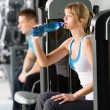 Young woman at gym drink water — Stock Photo
