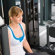 Young woman at fitness center sitting machine — Stock Photo #9776518
