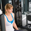 Royalty-Free Stock Photo: Young woman at fitness center sitting machine