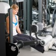 Stock Photo: Young woman exercise legs at fitness center