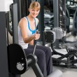 Young woman at fitness center exercise machine — Stock Photo #9776521