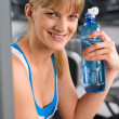Smiling woman with bottle of water — Stock Photo