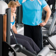 Personal trainer with young woman at gym — Stock Photo