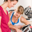 Young women on treadmill giving instructions - Stock Photo
