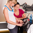 Stock Photo: Young female friends chatting in fitness center