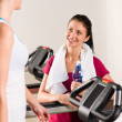 Young female friends chatting in fitness center — Stock Photo