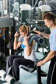 Fitness centrum mladá žena cvičení s trenérem — Stock fotografie