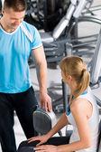 Personal trainer con la giovane donna in palestra — Foto Stock