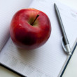 Apple lay on notebook next to pencil — Stockfoto #8869411
