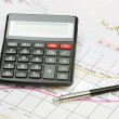 Calculator and pen on a financial charts — Stock Photo