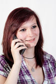 Young redhead woman is talking to someone over the smartphone - isolated on white background — Stock Photo