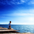 Young man relax siting on pier — Stock Photo #10486829