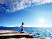 Young man relax siting on pier — Stock Photo