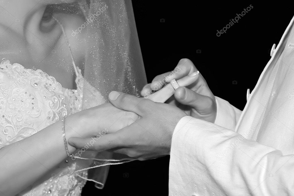 Close-up groom puts wedding ring on bride's finger. Black and white. — Stock Photo #10570883