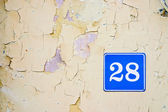 Number twenty eight in the old wall — Stock Photo