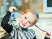 Child holds pigtails — Stock Photo