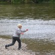 Boy throwing stone into the river — Stock Photo #8443608