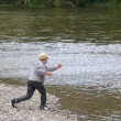 Boy throwing stone into the river - Stock Photo