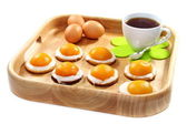 Easter biscuits and a cup of tea on wooden tray. — Stock Photo