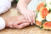 Hands beside a bouquet — Stock Photo