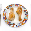 Roasted chicken legs on plate with fork and knife - Stock Photo