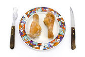 Roasted chicken legs on plate with fork and knife — Stock Photo