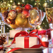 Elegant  holiday table setting with red ribboned gift - Stock Photo