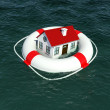 Home and lifebuoy in water - Stock Photo