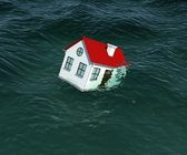 House with red roof sinks in water — Stock Photo