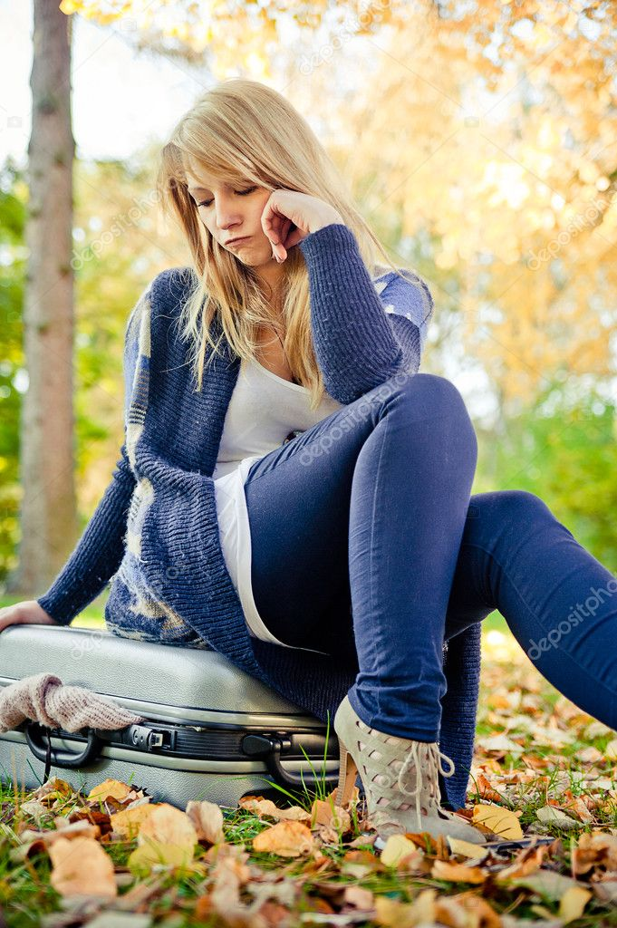 Blonde woman trying to close her suitcase in a park — Stock Photo #9689640