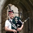 Stock Photo: Bagpiper under Archway