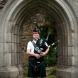 Royalty-Free Stock Photo: Bagpiper under an medieval Archway