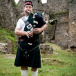 Bagpiper in an old castle — Stock Photo