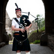 Stock Photo: Bagpiper in mediaval Castle