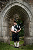 Bagpiper under an medieval Archway — Stock Photo