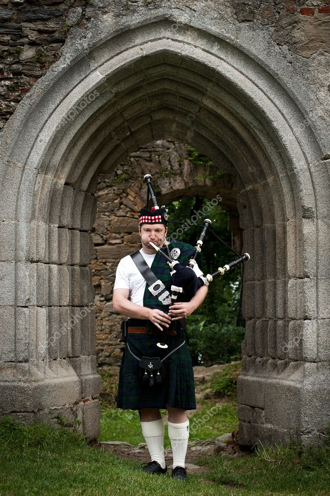 Man with bagpipe playing under an medieval Archway — Photo #9695658