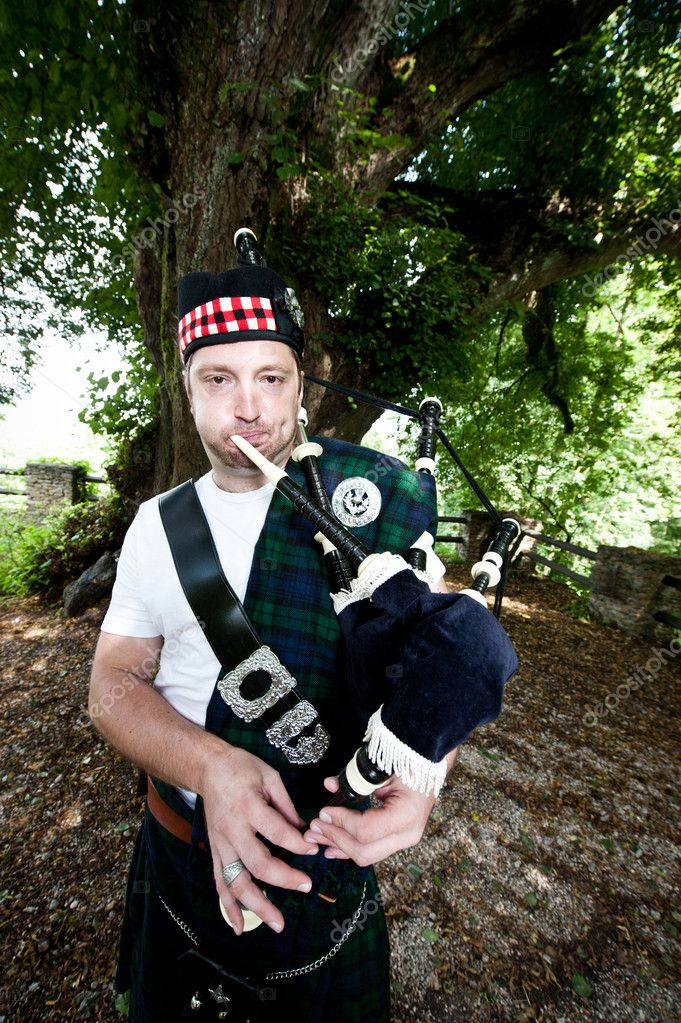 Scottish Bagpiper in front of a Tree — Stock Photo #9695795