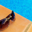 Sunglasses laying  by the  pool — Stock Photo