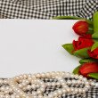 Red tulips with pearls strand and blank card — Stock Photo