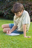 School boy writting in note book — Stock Photo
