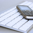 Mobile phone over laptop keyboard — Stock Photo