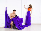The man sews to the woman a lilac dress — Stock Photo