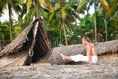 Yoga angusthasana pose on the beach — Stock Photo