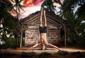 Yoga head stand pose near fisherman hut — Stock Photo