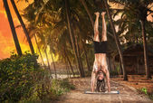 Yoga handstand pose at sunset — Stock Photo