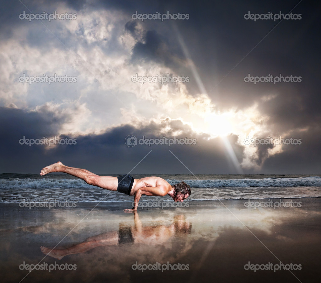 Yoga Mayurasana peacock handstand balancing pose by fit man on the beach near the ocean at dramatic sunset sky — Stock Photo #10403814