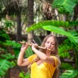 Girl playing the bamboo flute - Stock Photo