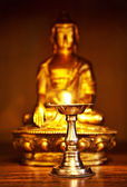 Golden Buddha with oil lamp — Stock Photo
