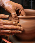 Hands of a potter, creating an earthen jar on the circle — Foto Stock