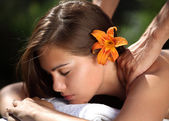 Young woman lying on massage table at spa, outdoors — Stockfoto